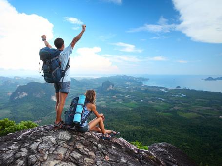 Фото Радостные юноша и девушка с рюкзаками за спинами, покорившие горную вершину