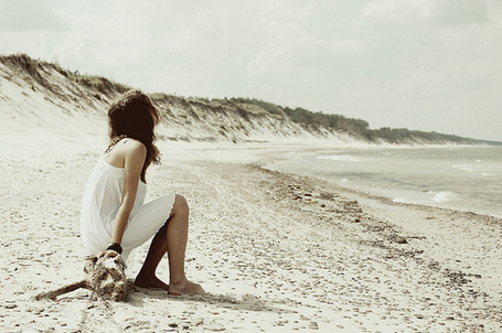 Фото Девушка в белом платье сидит на бревне на берегу моря