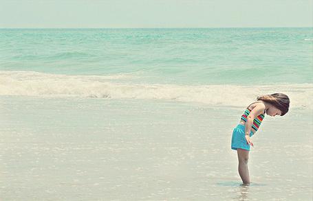 Фото Девочка стоит в море смотря в низ