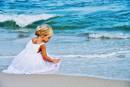 Фото Девочка сидит на берегу моря в белом платьице