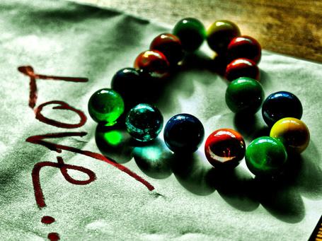 Фото Разноцветные, стеклянные шарики, выложенные на салфетке в форме сердечка и надписью 'Love / Любовь'