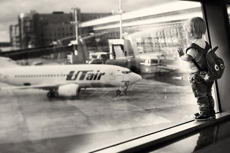 Фото Ребёнок стоит на полочке огромного окна, выходящего на стоянку самолетов аэропорта, работа фотографа Юлии Отто
