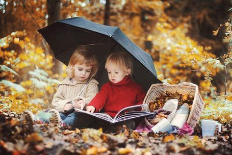 Фото Дети сидят под зонтом на осенних листьях и листают книгу, работа фотографа Юлии Отто