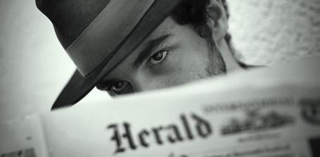 Фото Парень в шляпе смотрит поверх газеты (Herald)