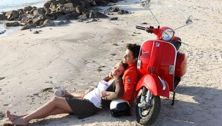 Фото Девушка в объятиях парня, прислонившегося спиной к красному мотороллеру, находятся на песчаном морском пляже