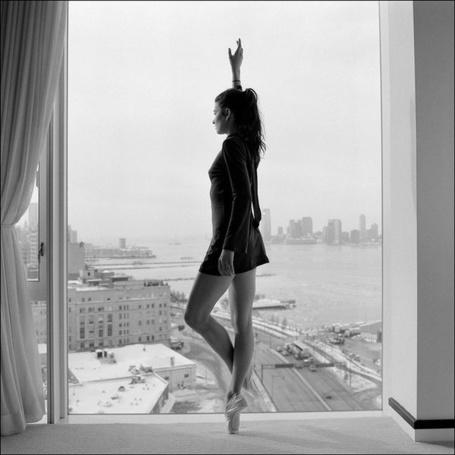 Фото Балерина стоит у окна с видом на город, фотограф  Дэйн Шитаги / Dane Shitagi