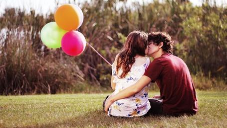 Фото Девушка. держащая в руке разноцветные надувные шарики, целуется с парнем, сидя на траве