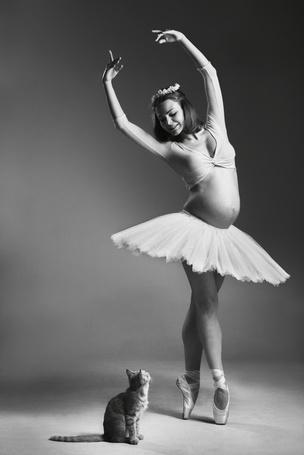 Фото Беременная блерина, стоит на носочках, кошка внимательно наблюдает за ней