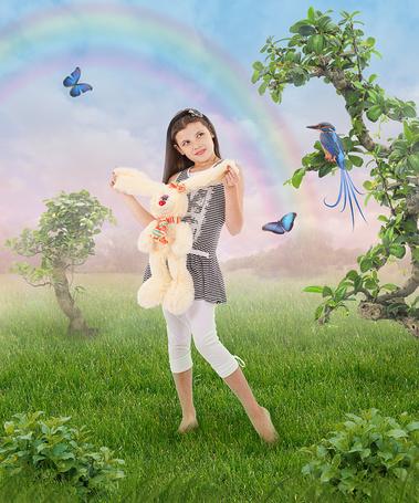 Фото Девочка с игрушечным кроликом в саду, рядом летают бабочки и сидит птица