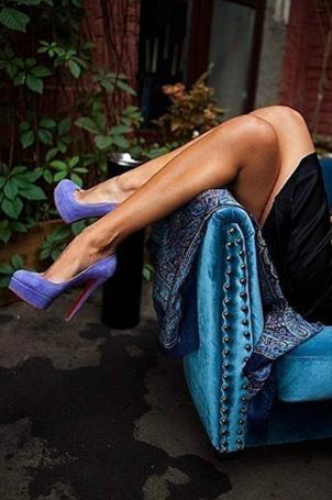 Фото Девушка сидит в голубом кресле, закинув ногу на ногу