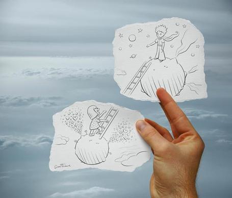 Фото Мужская рука держит два листка с рисунками на фоне неба, на одном нарисован мальчик стоящий на маленькой планете, а на другом девочка пытающаяся по лестнице перебраться к нему
