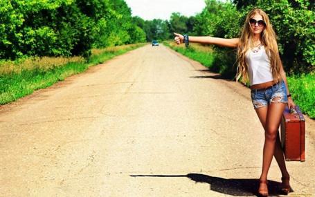 Фото Девушка с чемоданом в руках голосует на дороге