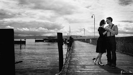 Фото Парень с девушкой стоят в обнимку на морском пирсе на фоне пасмурного неба