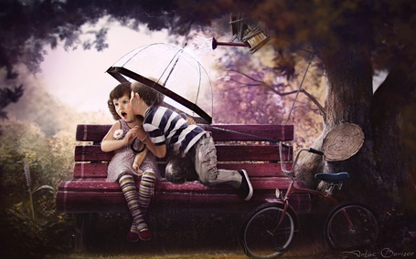 Фото Мальчик целует девочку в парке на красной скамейке под зонтиком от дождя