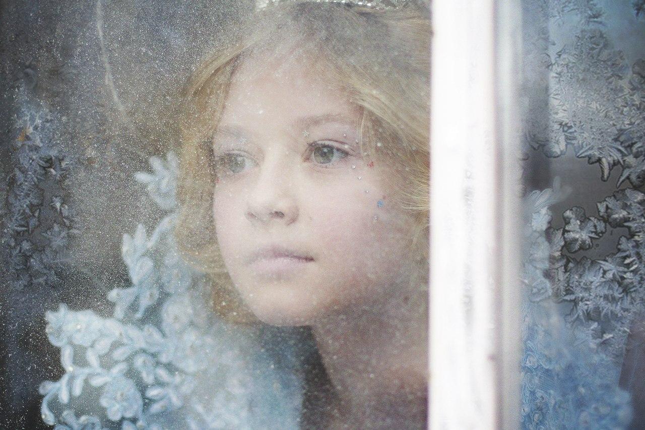 Девушка за замерзшим стеклом со снежными узорами, фотограф Маша Хозяинова