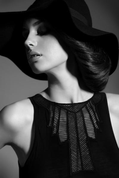 Фото Эффектная девушка в черной одежде и черной шляпе повернула голову в сторону
