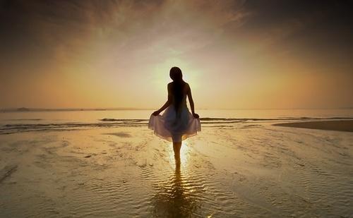 Фото Девушка в белом платье идет по морскому берегу на фоне заката