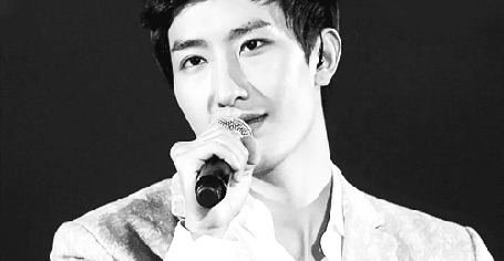 Фото Чжоу Ми / Zhou Mi улыбается держа микрофон у рта