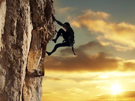Фото Альпинист поднимается по отвесной скале на фоне заката