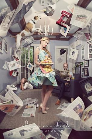Фото Девушка стоит по середине комнаты с подносом пирожных в руках, на заднем плане мужчина читает газету, а ребёнок смотрит телевизор, вокруг них летают разные предметы и собака, фотограф Shawn van Daele / Шон Ван Дэле