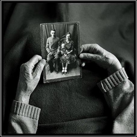 Фото Старушка держит в руках семейное фото