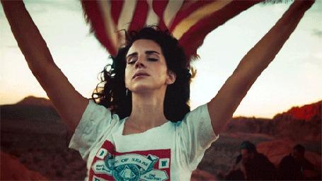 Фото Певица Лана Дель Рей / Lana Del Rey с закрытыми глазами держит американский флаг, который раздувается по ветру