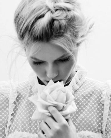 Фото Девушка прикасается губами к розе