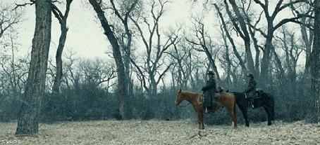 Фото Двое мужчин сидят верхом на лошадях во время снегопада