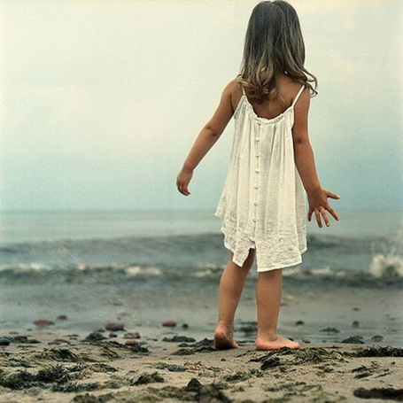 Фото Девочка у моря стоит к нам спиной