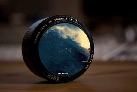 Фото Объектив от камеры Canon, где отображен серфингист на волне