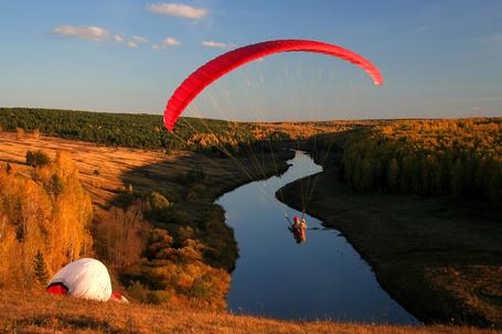 Фото Парашютист завис над руслом реки с берегами, покрытыми осенними деревьями, работа фотографа Александра Клековкина