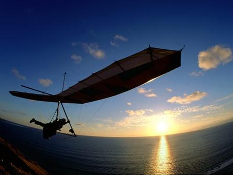 Фото Дельтапланерист над морем и солнцем