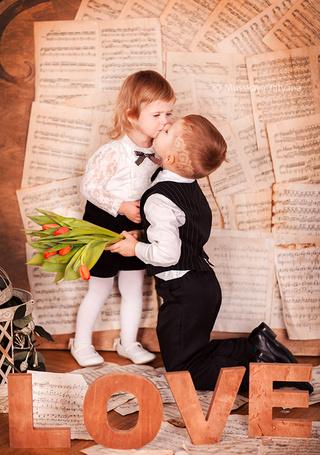 Фото Мальчик, стоя на коленях с цветами в руке целует девочку на фоне нотных листов (LOVE / Любовь) (© Felikc), добавлено: 22.02.2013 11:28