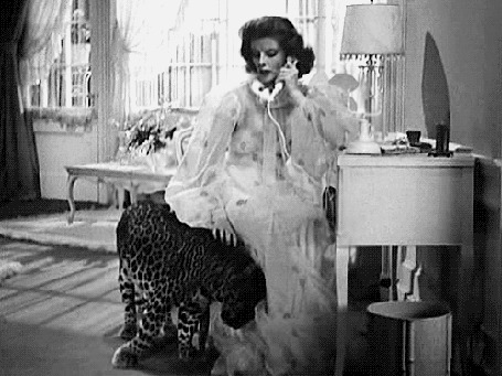 Фото Кэтрин Хепберн / Katharine Hepburn разговаривает по телефону и гладит леопарда из фильма 'Воспитание крошки' / 'Bringing Up Baby'