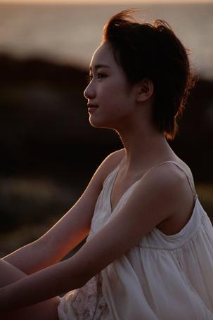 Фото Кудо Харука / Kudo Haruka в белом платье сидит и смотрит в сторону от камеры. Вдалеке виднеется море