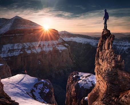 Фото Мужчина стоит на самой вершине пика горы, другой мужчина на краю перед горным ущельем, оба встречают рассвет, фотограф Max Rive