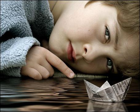 Фото Маленький мальчик лежит возле бумажного кораблика, плывущего в луже воды (© ), добавлено: 26.02.2013 17:31