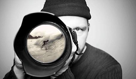 Фото Мужчина держит в руках фотоаппарат, в объективе которого серфингист катается на волнах