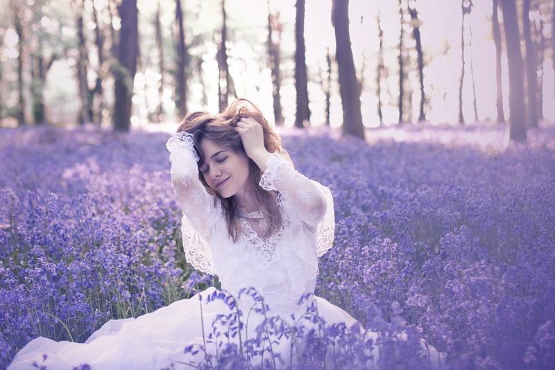 Девушка в белом платье сидит на поляне среди фиолетовых полевых цветов