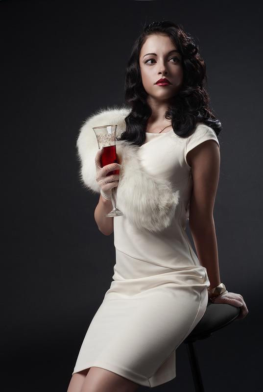 Фото Девушка с распущенными волосами в белом платье и меховой накидке на плече сидит на черном стуле с бокалом вина в руке