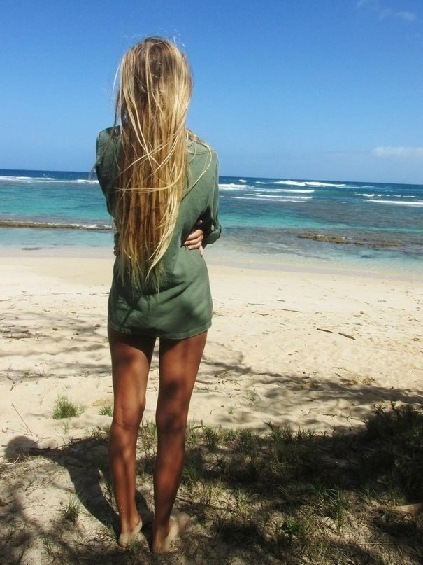 Стоит на пляже и смотрит на море и небо