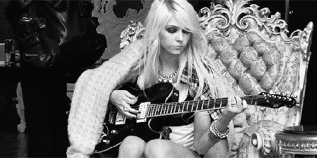 Фото Американская актриса, рок-певица, гитаристка и фотомодель Тейлор Момсен / Taylor Momsen сидит на кресле и играет на гитаре