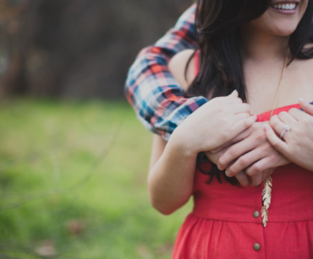 Фото Парень сзади обнимает улыбающуюся девушку в красном платье