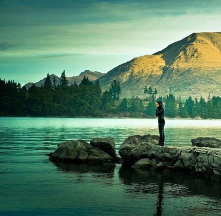 Фото Девушка стоит на камнях у воды на фоне чудного пейзажа
