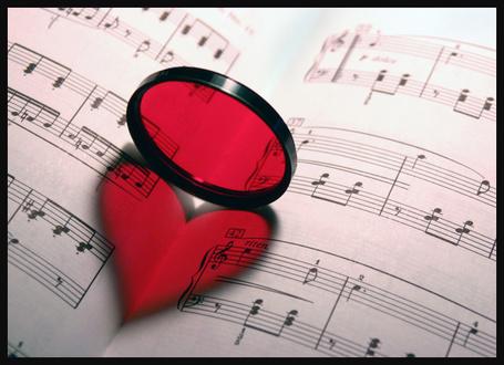 Фото Красное стеклышко стоит на ребре создавая иллюзию сердечка на сгибе нотной тетради (© eka_terinka), добавлено: 06.03.2013 07:16