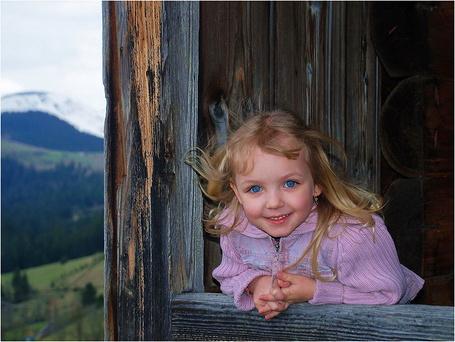 Фото Девочка с синими глазами, выглядывает в раскрытое окно и улыбается