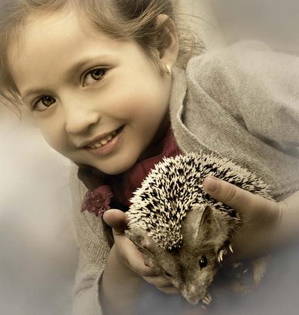 Фото Девочка держит в руках ежика и улыбается