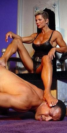 Фото Девушка качек сидит в кресле и наступила ногой на голову мужчине , который склонил голову к полу