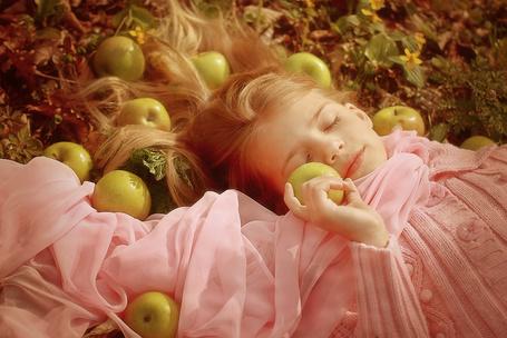 Фото Девочка в розовых кофточке и шарфе, лежит между яблок, с яблоком в руке