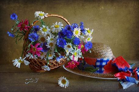 Фото На столе стоит плетеная корзинка с цветами, и лежит соломенная шляпка с цветным бантом (© Akela), добавлено: 07.03.2013 18:47